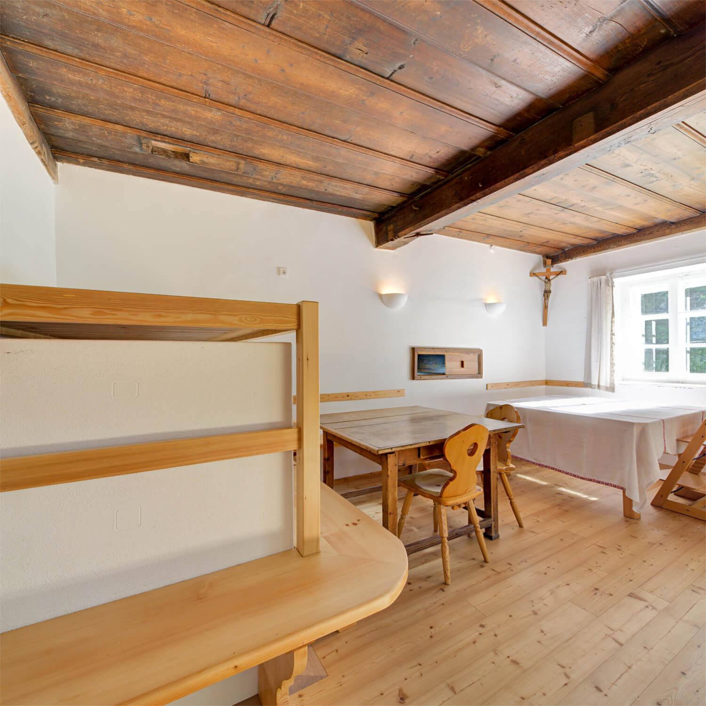 Ferienhaus Maar1 am Goldberg - Stube mit gemauertem Ofen und großer Ofenliegebank, mit Durchreiche in die Küche