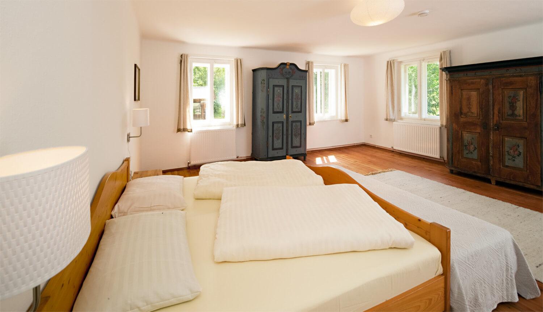 Ferienhaus Maar1 am Goldberg - Zimmer Jakob, großes Schlafzimmer mit vier Fenstern, Süd-Ost-Ausrichtung, Doppelbett und zwei Einzelbetten