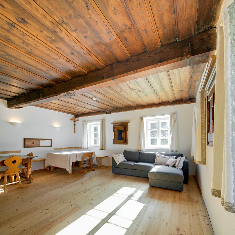 Ferienhaus Maar1 am Goldberg - Stube mit bis zu zwölf Sitzgelegenheiten an zwei großen Tischen, gemütlicher Couch und großer Liegefläche auf gemauertem Ofen, Fernseher